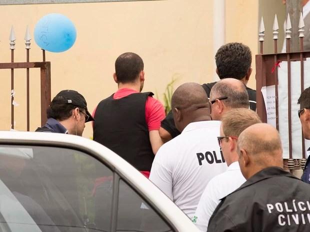 Guilherme Longo sai de viatura e entra na casa onde morava com Natália Ponte e Joaquim (Foto: Érico Andrade/G1)