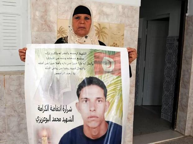Manoubia Bouazizi, mãe de Mohamed Bouazizi, que passou a ser lembrado como motivador da revolta na Tunísia, segura faixa com uma foto do filho em foto de 15 de novembro de 2011 (Foto: Fetih Belaid/AFP)