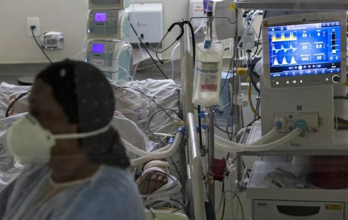 Profissional de saúde cuida de paciente com Covid-19 no Hospital Emílio Ribas, em São Paulo, no dia 17 de março. — Foto: Miguel Schincariol/AFP