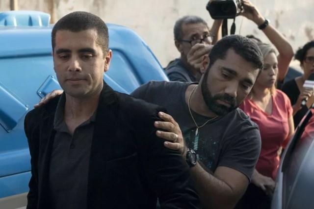 O médico Denis Cesar Barros Furtado, o Dr. Bumbum, é escoltado pela polícia após sua prisão no Rio de Janeiro (Foto: Leo Correa/AP)