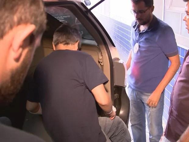Cercado por curiosos e jornalistas no hospital, Hugo entra na viatura  (Foto: Reprodução / TV TEM)