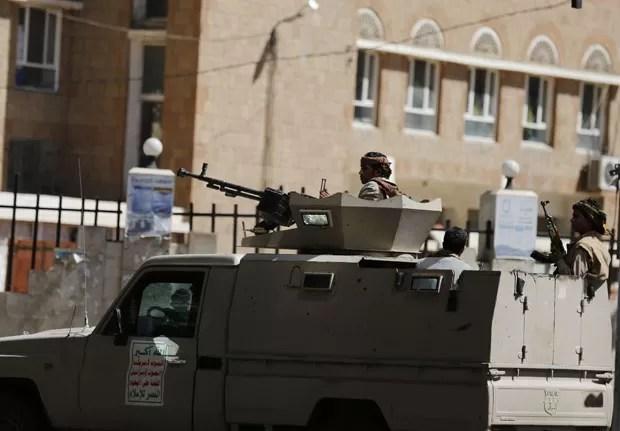 Combatentes houthi são vistos perto das embaixadas da Arábia Saudita e dos Emirados Árabes em Sanaa neste sábado (14); as duas representações foram fechadas pelos países (Foto: Khaled Abdullah/Reuters)