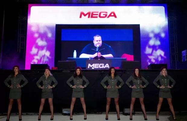 Fundador do Megaupload, Kim Dotcom aparece em uma tela grande durante o lançamento do site de compartilhamento de arquivos Mega em sua mansão em Auckland, na Nova Zelândia, neste domingo (20)  (Foto: AP)