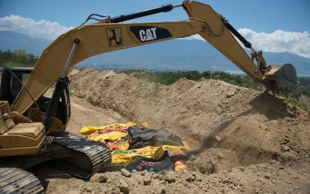 Escavadeira é usada para abrir vala comum para enterrar mortos nos arredores de Palu — Foto: Bay Ismoyo / AFP