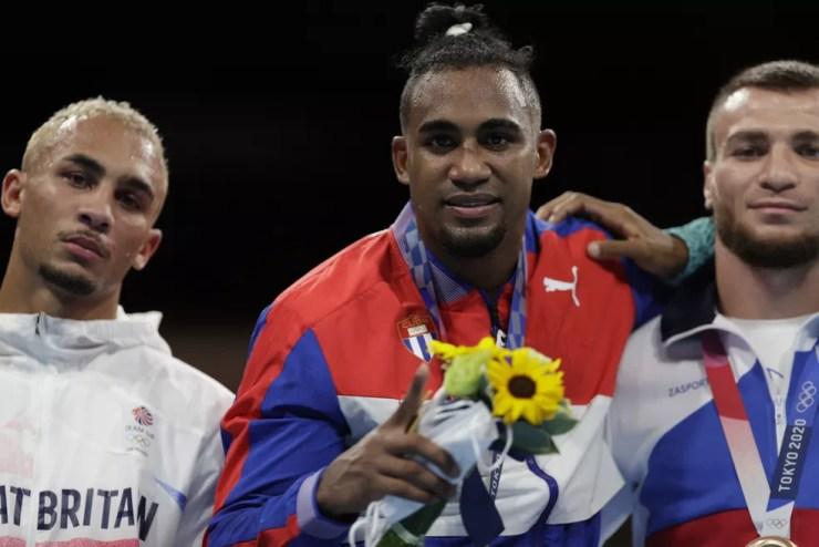 Benjamin Whittaker (esq.) de cara amarrada no pódio ao lado do campeão Arlen Lopez e do medalha de bronze Loren Dominguez — Foto: REUTERS/Ueslei Marcelino