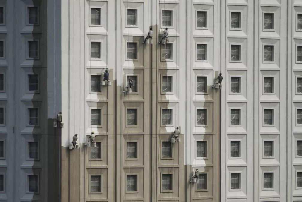 13 de julho - Trabalhadores chineses pintam lateral de um prédio em Shenyang, província de Liaoning, na China (Foto: Fred Dufour/AFP)