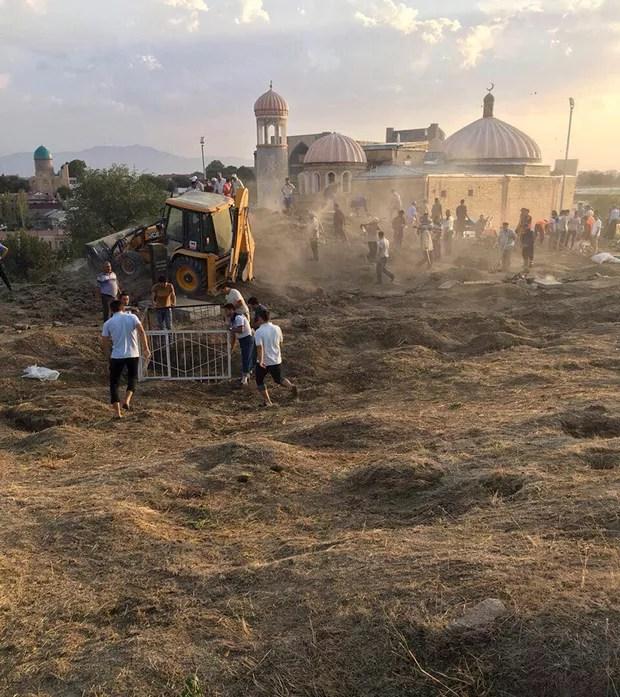 Operários fazem limpeza de área do cemitério central em Samarkand, no Uzbequistão, na quinta-feira (1) (Foto: News Agency Ferghana.Ru/AP)