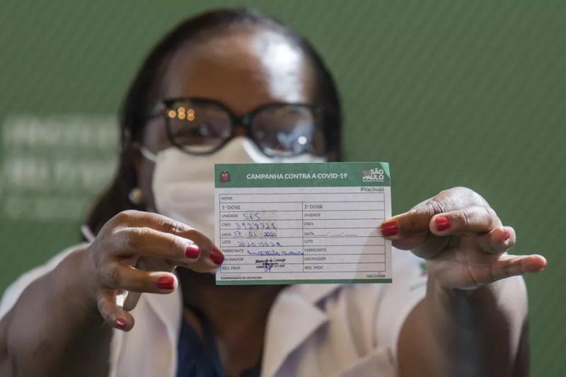 A enfermeira Mônica Calazans, de 54 anos, mostra seu cartão de vacinação após ser a primeira brasileira a receber a vacina CoronaVac no Hospital das Clínicas, em São Paulo, neste domingo (17)  — Foto: Carla Carniel/AP