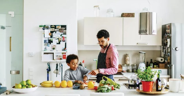 A father and son at home in the kitchen helping each other prepare some lunch. (Foto: Getty Images)