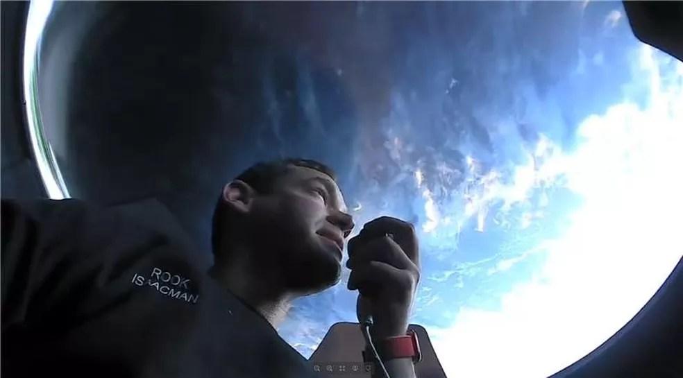 Jared Isaacman, bilionário que bancou a missão, olhando para a Terra através do domo da cápsula — Foto: Redes sociais/Inspiration4