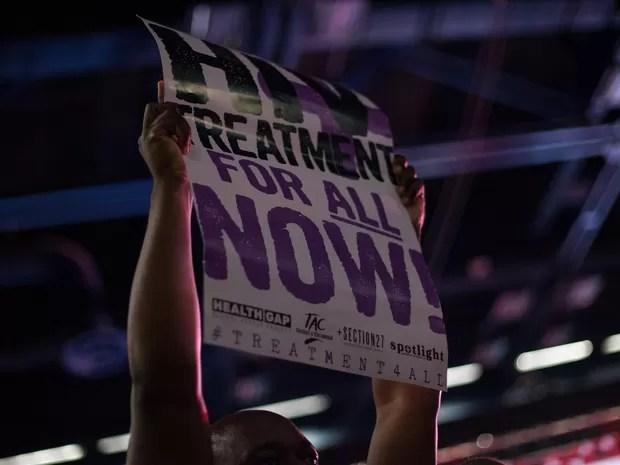 Ativista segura um cartaz pedindo tratamento para todos com HIV  (Foto: Matthew Kay/AFP)