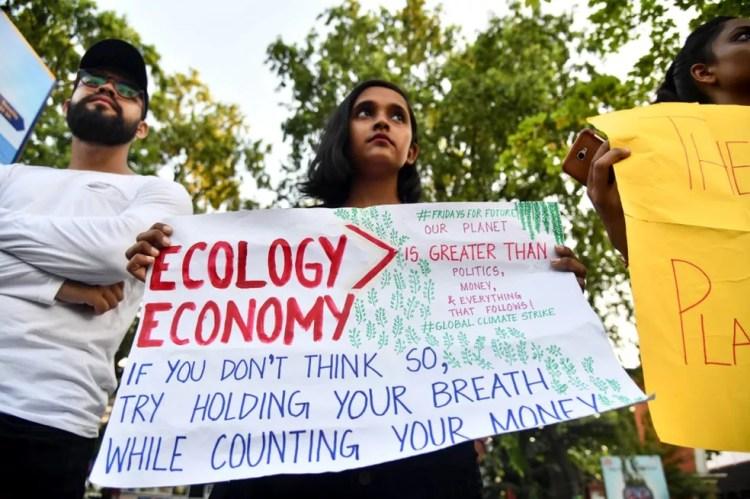Greve pelo Clima: Na Índia, uma jovem manifestante empunha um cartaz defendendo a economia ecológica: 'Nosso planeta é maior que a política, o dinheiro, e tudo que está relacionado a isso'. A manifestação ocorre nesta sexta (20), em Guwahati. — Foto: Biju Boro/AFP