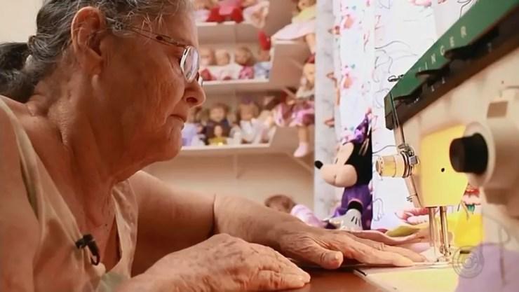 Aposentada faz o vestido das bonecas na máquina de costura em Bady Bassitt (Foto: Reprodução/TV TEM)