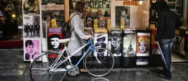 Jovem olha discos de vinil junto a sua bicicleta
