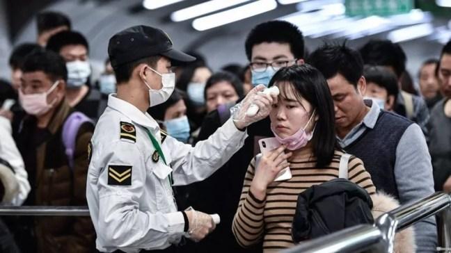 Viajantes passam por teste de temperatura corporal em aeroporto para detectar sintoma de febre causada por Coronavírus. — Foto: Getty Images