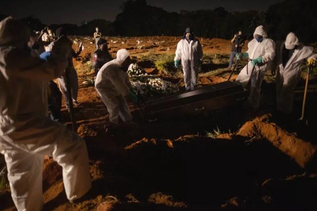 Coveiros usando equipamento de proteção são vistos trabalhando em sepultamento noturno no cemitério da Vila Formosa, Zona Leste da cidade de São Paulo, nesta sexta-feira (26) — Foto: ETTORE CHIEREGUINI/ESTADÃO CONTEÚDO
