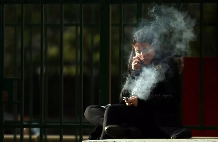 Jovem fuma cigarro eletrônico enquanto fala ao celular em Buenos Aires; público jovem é o mais vulnerável aos atrativos do dispositivo  (Foto: REUTERS/Marcos Brindicci)