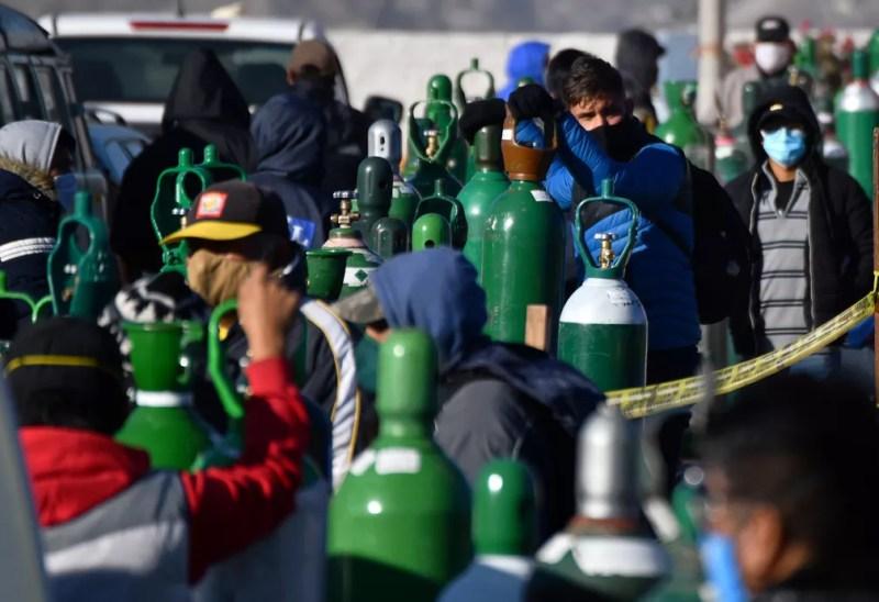 Familiares de pacientes com Covid-19 fazem fila para recarregar cilindros de oxigênio nos arredores de Arqeuipa, no Peru, em 23 de julho  — Foto: Diego Ramos/AFP