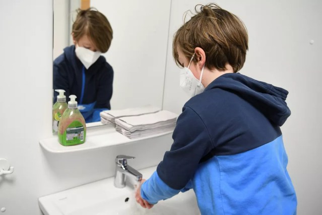 Foto mostra criança lavando as mãos em escola primária de Berlim, no primeiro dia de retorno em meio ao relaxamento das restrições contra a Covid-19, no dia 22 de fevereiro. — Foto: Annegret Hilse/Reuters