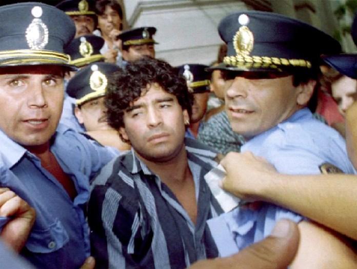 Diego Maradona é acompanhado por policiais após deixar tribunal em Mercedes, na Argentina, em março de 1994. Ele estava respondendo a processo por ter agredido jornalistas diante de sua casa dois meses antes — Foto: Reuters/Arquivo