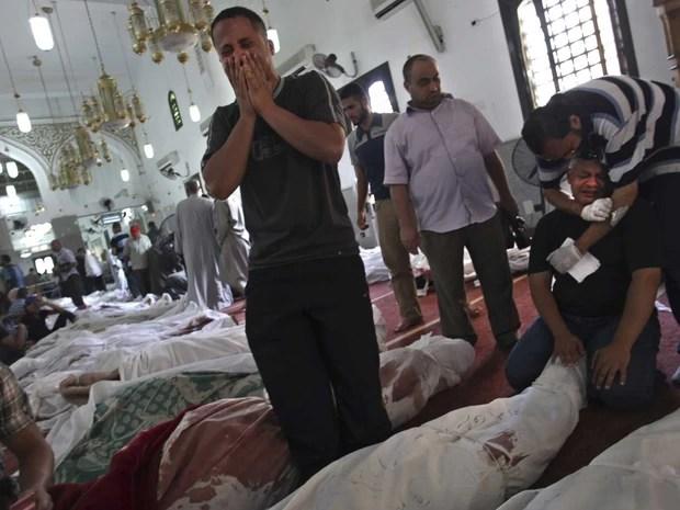 Homens choram à beira dos corpos de familiares mortos nos conflitos da véspera no Cairo. Ao lado de diversas outras vítimas, os corpos foram reunidos na mesquita El-Iman, no bairro de Nasr (Foto: Khalil Hamra/AP)
