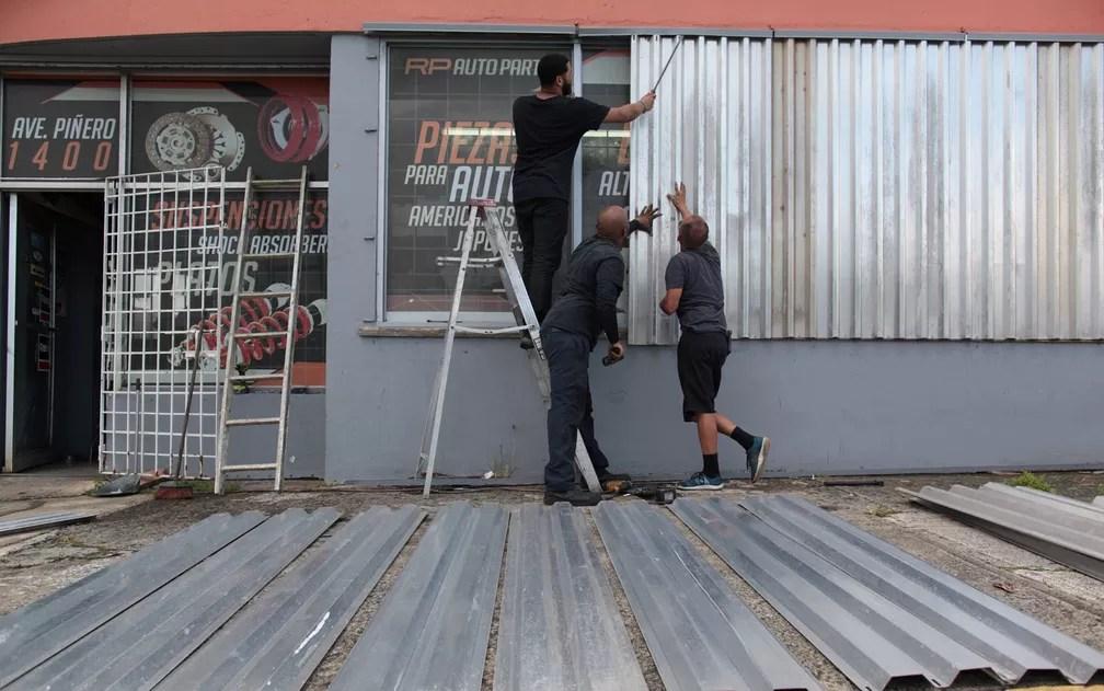 Funcionários colocam placas para proteger janelas de oficina em San Juan, Porto Rico, antes da passagem do furacão Irma, na terça (5) (Foto: Reuters/Alvin Baez)