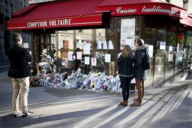Pessoas param para olhar flores, velas e mensagens em homenagem às vítimas em frente ao café Comptoir Voltaire, um dos locais dos atentados terroristas em Paris, na França (Foto: Charles Platiau/Reuters)