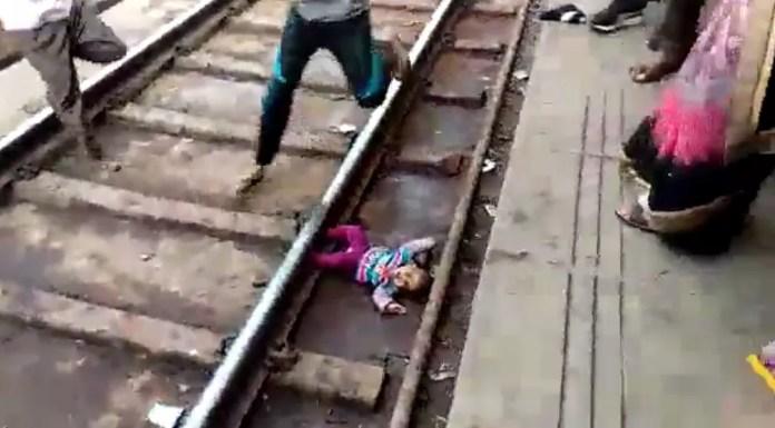 Homem pula em trilhos de trem de estação na Índia para resgatar bebê que caiu — Foto: NNIS / AFP