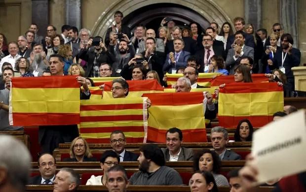 Deputados do Partido Popular (PP) exibem as bandeiras espanholas e catalãs após votação do parlamento catalão que aprovou início do processo de separação (Foto: Albert Gea/ Reuters)