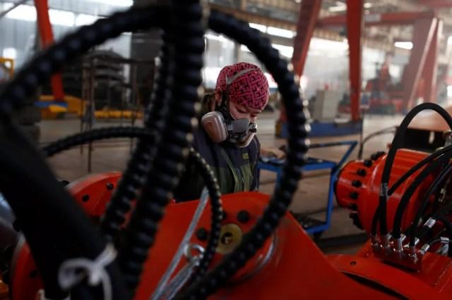 Uma mulher trabalha em fábrica na província de Hebei, China (Foto: Thomas Peter / Reuters)