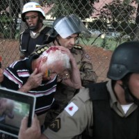 Belo Horizonte – Homem ferido na região do estádio do Mineirão é auxiliado por policiais; estádio recebeu neste sábado jogo México x Japão, válido pela Copa das Confederações (Foto: Sergio Moraes/Reuters)