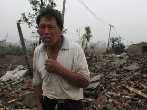 Homem lamenta destruição de casa após passagem de tornado em Yancheng, na provínce de Jiangsu, na China, na quinta-feira (23)  (Foto: China Dailyvia Reuters)