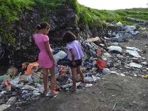 Meninas brincam em meio ao lixo, que ainda é visível, no Lixão do Roger, em João Pessoa. (Foto: Aline Oliveira/G1-PB)