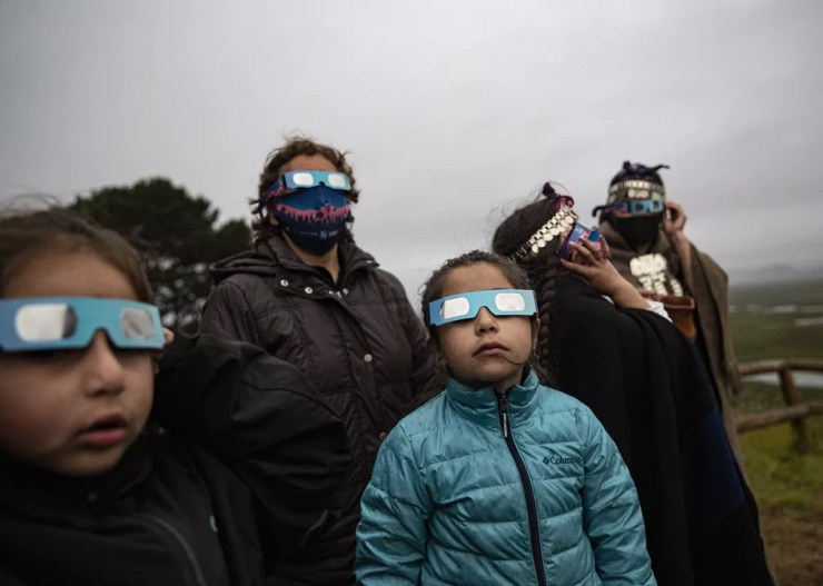 Família indígena Mapuche usa óculos especiais para ver eclipse solar total em Carahue, na região chilena de Araucania nesta segunda-feira (14). — Foto: Esteban Felix/AP