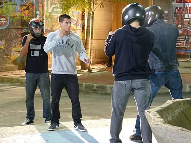 Duca é surpreendido por três caras de capacete na praça (Foto: Malhação / TV Globo)