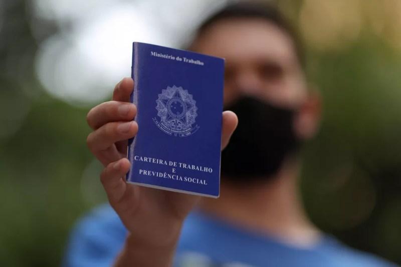 Homem segura carteira de trabalho enquanto procura emprego — Foto: Amanda Perobelli/Reuters/Arquivo