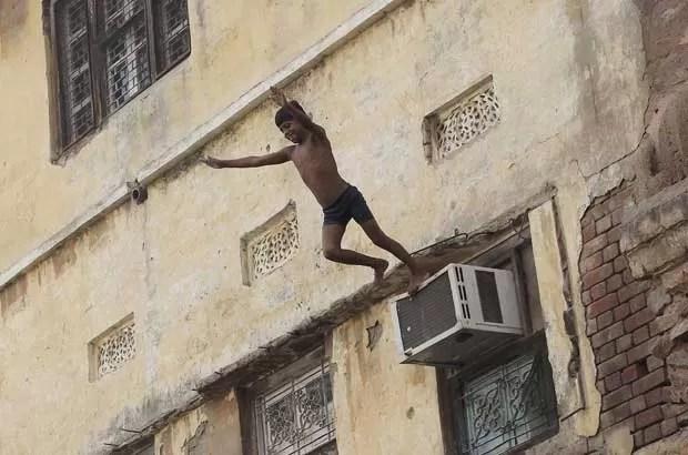 Garoto usa ar-condicionado como trampolim para saltar em rio. (Foto: Adnan Abidi/Reuters)