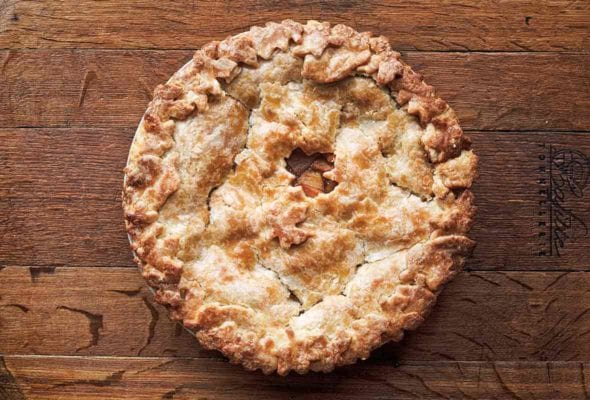 A baked hot buttered rum apple pie on a wooden board.