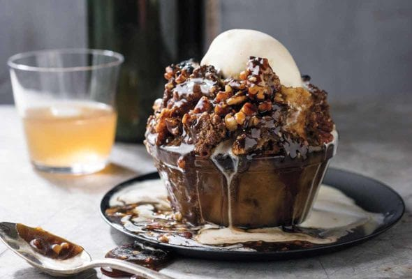 Glass bowl filled with pecan pie bread pudding, caramel sauce, bourbon-vanilla ice cream on a marble table
