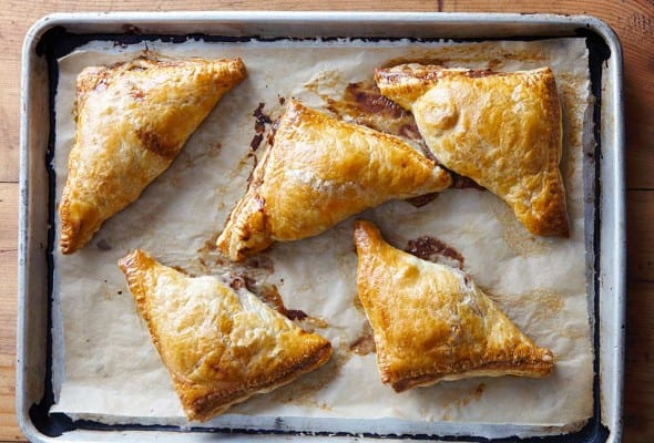 Five pear turnovers on a piece of parchment in a rimmed baking sheet.
