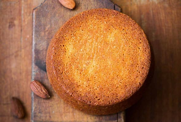 A round flourless almond cake on a wooden baking paddle with almonds scattered around it