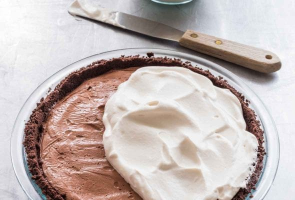 A dark chocolate cream pie half covered with whipping cream with a bowl of whipping cream and a spatula resting beside the pie.
