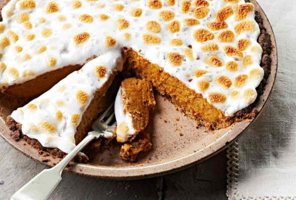 A pumpkin sweet potato pie in a brown pie dish with a fork resting inside and a linen napkin next to the pie dish.