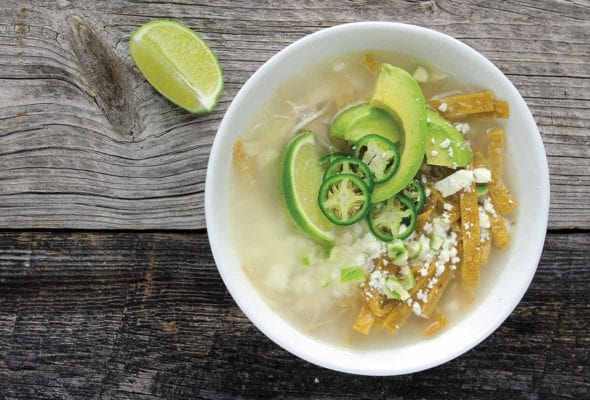 A white bowl filled with broth, avocado slices, lime wedges, cheese, and tortillas strips