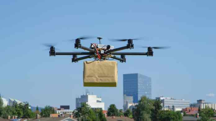 A five-rotor drone lifts a package into the air.