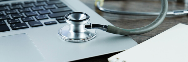 Doctor desk table with stethoscope ,blank notebook and laptop co