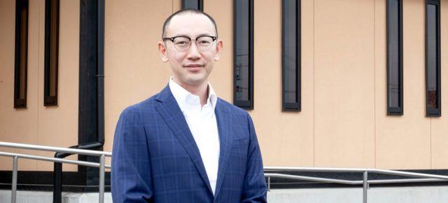 店舗の前で笑顔でたたずむ上野社長