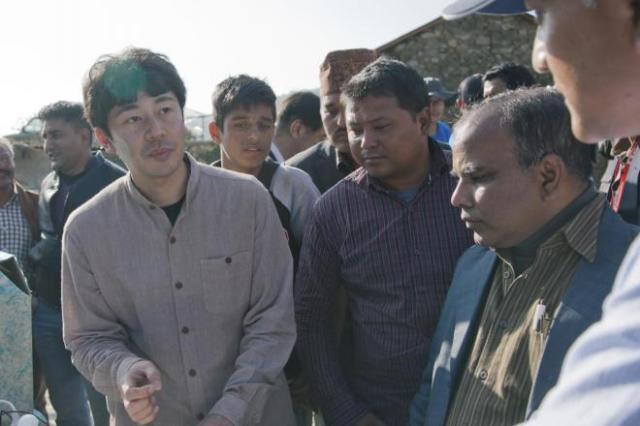 ネパールで土木工事の要らない水力発電機の説明をする菊池伯夫さん(左)=茨城製作所提供