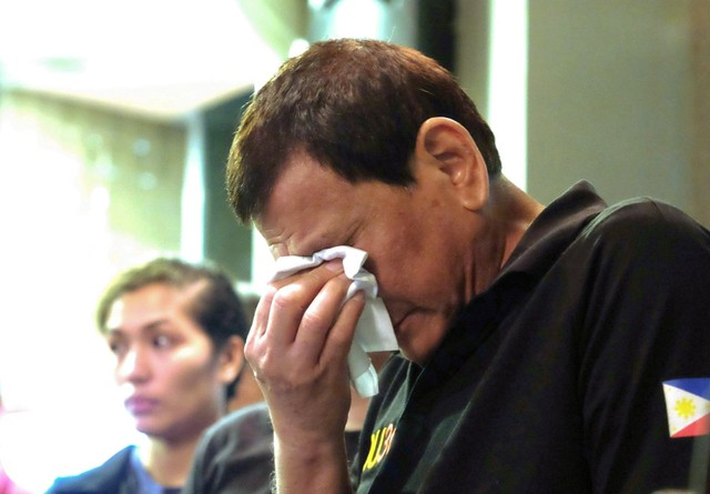 President Rodrigo Duterte weeps as he comforts family members of fire victims in Davao city in Philippines, December 24, 2017. Credit: Reuters/Presidential Palace