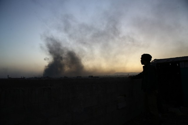 A man watches as smoke rises from Harasta area, as seen from Douma, in the eastern Damascus suburb of Ghouta, Syria November 14, 2017. Credit: Reuters/Bassam Khabieh/Files